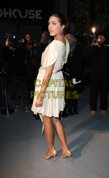 AMBER LE BON.Attending The Love Ball during London Fashion Week, the Roundhouse, Chalk Farm Road, London, England..February 23rd 2010.LFW arrivals full length beige white  ruched cream dress gold shoes white looking over shoulder LeBon side .CAP/ROS.©Steve Ross/Capital Pictures.