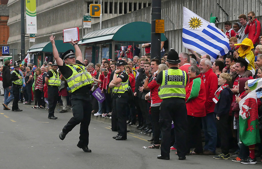A Police officer entertains the crowd while they wait for the  Wales team bus to arrive <br /> <br /> Photographer Ian Cook/CameraSport<br /> <br /> Rugby Union - 2015 Rugby World Cup - Wales v Uruguay - Sunday 20th September 2015 - Millennium Stadium - Cardiff<br /> <br /> &copy; CameraSport - 43 Linden Ave. Countesthorpe. Leicester. England. LE8 5PG - Tel: +44 (0) 116 277 4147 - admin@camerasport.com - www.camerasport.com