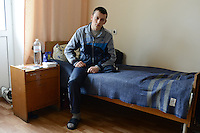 Refat, 19, a Ukrainian soldier from Crimea, sits on his hospital bed at the Main Military Clinical Hospital of the Ministry of Internal Affairs in Kiev, Ukraine on April 8, 2014.  Refat was shot in the left knee by a sniper on February 20, 2014 while trying to maintain a line of soldiers on orders and had the lower part of his left leg amputated from above the knee.<br /> <br /> &quot;We had orders to stand in the line.  In the morning, it was quite calm and silent and then the protesters started to attack and they threw a grenade and I walked away from there and then I felt a sniper's bullet in my knee.  It was the morning of February 20 and we were unarmed.  I was standing with just a shield.  That morning there was shooting from both sides.  The criminal case is still open and nobody knows why they were shooting.  I blame the president.  I want a normal president and stability to come to Ukraine.  I want to stay in Kiev and enter the main university and study law.  I want to become a prosecutor.  I want things to be tranquil here in Ukraine.&quot;