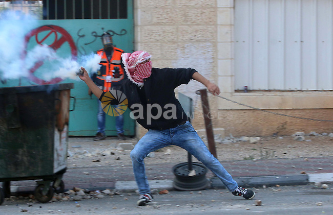 A Palestinian protester throws back a tear gas canister towards Israeli security forces during clashes in the West Bank town of Bethlehem on October 9, 2015. Tension and protests rose after an Israeli man on 09 October stabbed four Palestinians in southern Israel, in what is being seen as a revenge attack, officials said. On 08 October several violent incidents happened, including stabbings which left eight Israelis injured, one Palestinian was killed in East Jerusalem and six in the Gaza Strip in clashes with the army while at least six were injured on the West Bank. Photo by Muhesen Amren