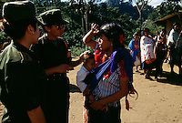 Women soldiers talk with a young Mayan mother and check the health of a young child at Maajon Pepintic near Pholo in Mexico. The military presence is strong in Chiapas, but soldiers are attempting to win the trust of local Indians. Social labor camps opened Dec 23, 1997 after the massacre in nearby Mahomut west of San Cristobal. Now soldiers offer medical treatment and dental care. They repair schools and roads and prepare meals. Approximately 150 people are fed a day--3 meals a day in one camp. Children gave bananas to these soldiers in return. The region is in a conflict between the Zapatista guerrillas and PRI-the government military. Military checkpoints stop every car and search for weapons and demand identification. Of the 3.6 million people in Chiapas, Indians make up 900,000.