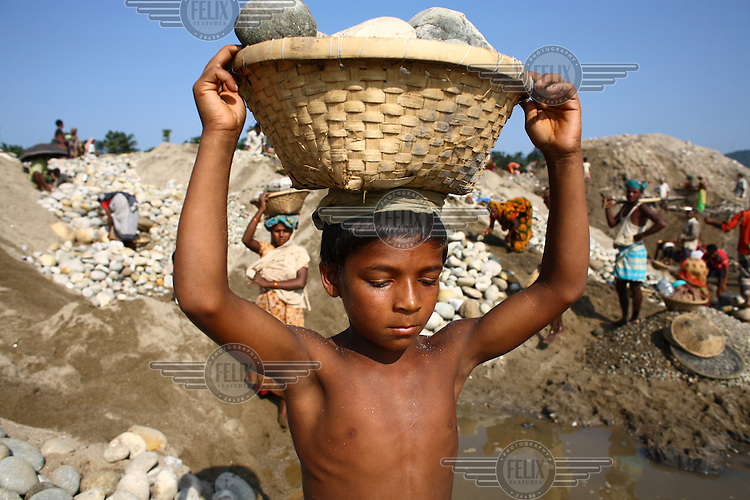 A child carries stones on his head at Bhollar Ghat. At least 10,000 people, including 2,500 women and over 1,000 children, are engaged in stone and sand collection from the Bhollar Ghat on the banks of the Piyain river. Building materials such as stone and sand, and the cement which is made from it, are in short supply in Bangladesh, and commands a high price from building contractors. The average income is around 150 taka (less than 2 USD) a day.