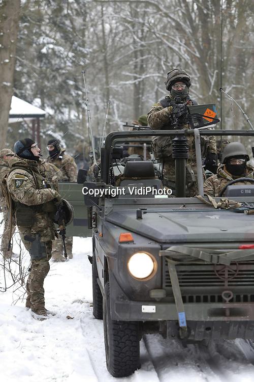 Foto: VidiPhoto<br /> <br /> SCHAARSBERGEN &ndash; Terwijl collega&rsquo;s bij de warme kachel een &lsquo;NAVO-vertegenwoordiger&rsquo; beschermen, staan en zitten de overige militairen dik ingepakt te kleumen in hun open voertuigen in de sneeuw. De bossen bij Schaarsbergen (gemeente Arnhem) vormden donderdag het decor voor de eindoefening van het Force Protection Peloton van het Bataljon Limburse Jagers uit Oirschot dat in maart vertrekt naar Afghanistan. De pantserinfanteristen werken in Afghanistan samen met Duitse militairen met als doel de achtergebleven (NAVO-)veiligheidsadviseurs uit 30 verschillende landen te beschermen bij hun werkzaamheden in Afghanistan. Die ondersteunen niet alleen Afghaanse veiligheidstroepen, maar ook verrichten ook advieswerk op het gebied van de infrastructuur om zo het land weer op te bouwen.