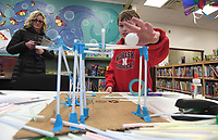 NWA Democrat-Gazette/J.T. WAMPLER Kai Thomsen, 11, shows off his creation while his mom Stacy Thomsen prepares to record Thursday Feb. 7, 2019 during an after school club at the Farmington Public Library called Readers and Dreamers. Kai made a roller coaster for a table tennis ball with straws and cardboard. The club meets the first Thursday of the month. For more information visit https://farmpl.org/
