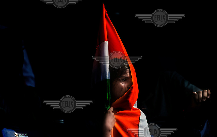 A cricket fan draped in an Indian flag waits for Sachin Tendulkar to come out to bat at his 200th (and last) test cricket match before his retirement at Wankhede Stadium in Mumbai.
