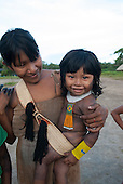 Aldeia Baú, Para State, Brazil. Kayapo woman with her baby in a traditional woven palm sling.