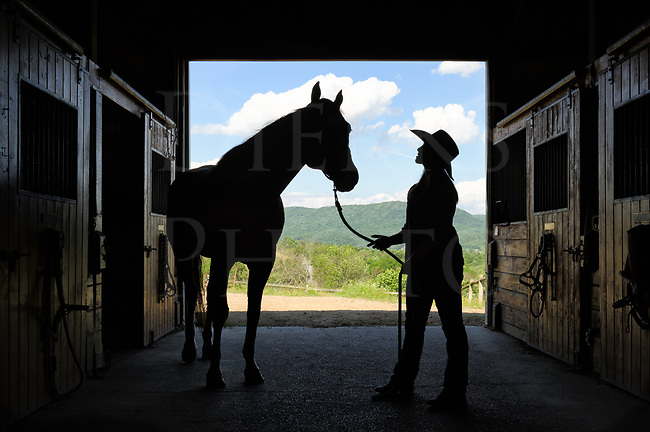 This barn door silhouette shows a young girl talking things through with her horse, getting things off her mind and into words that someone or something will hear. What the heartfelt matter is we don&rsquo;t really know, but for many centuries endless tears have been poured into horse&rsquo;s manes which certainly makes them good listeners. It&rsquo;s a good thing horses like us.<br /> <br /> I enjoy shooting silhouettes with horses and their people, especially with this stable door opening onto the hills and mountains of a beautiful Pennsylvania summer day. Many of the images such as this one can have good storytelling qualities with deep personal bonds very evident, and then the view becomes more than just a picture about the connection between horse and rider.
