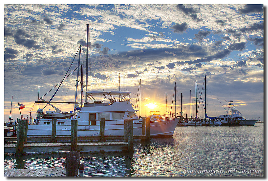 Sunrise over the harbor at Rockport, Texas, brings a new day and shrimp boats that have been out all night. Other boats, such as this houseboat, allow folks to sleep in the calm waters in this protected cove and enjoy life on the Texas Gulf coast. This Rockport image was taken on a cool October morning as storm clouds began to dissipate along the coast.