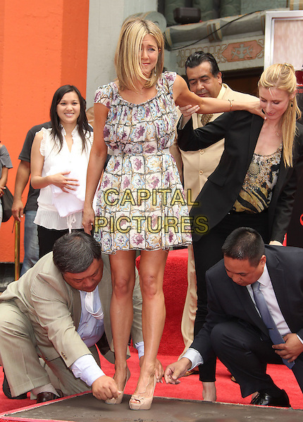 Jennifer Aniston.The Jennifer Aniston Hand and Footprints Ceremony held at The Grauman's Chinese Theatre in Hollywood, California, USA..July 7th, 2011.full length white grey gray purple floral print dress beige peep toe shoes step stepping balance funny.CAP/ADM/RE.©Russ Elliot/AdMedia/Capital Pictures.