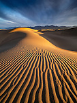 Storm light at sunrise illuminates the Mesquite Flats Sand Dunes in Death Valley National Park, California
