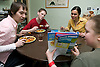 Family having lunch at home talking about where to go for their Summer holiday,