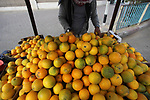 A Palestinian sells oranges, in Gaza City, on December 4, 2019. Photo by Mahmoud Ajjour