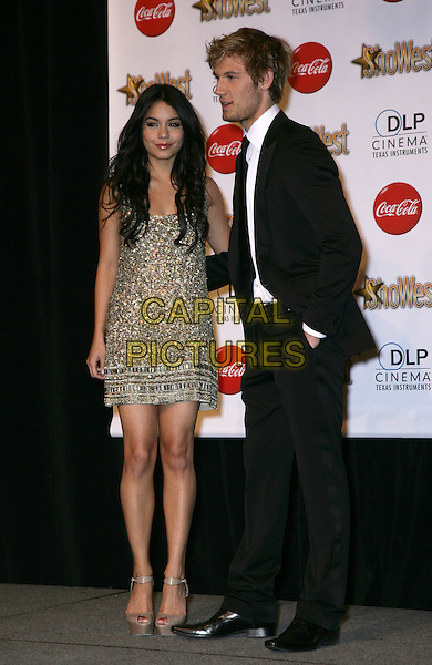 VANESSA HUDGENS & ALEX PETTYFER .SHOWEST Final Night Talent Awards at the Paris Resort Hotel and Casino,  Las Vegas, Nevada , USA,.18th March 2010..full length black suit tie hand in pocket white shirt  gold beaded jewel encrusted embellished dress brown peep toe platform shoes ankle strap side profile arm around .CAP/ADM/MJT.© MJT/AdMedia/Capital Pictures.
