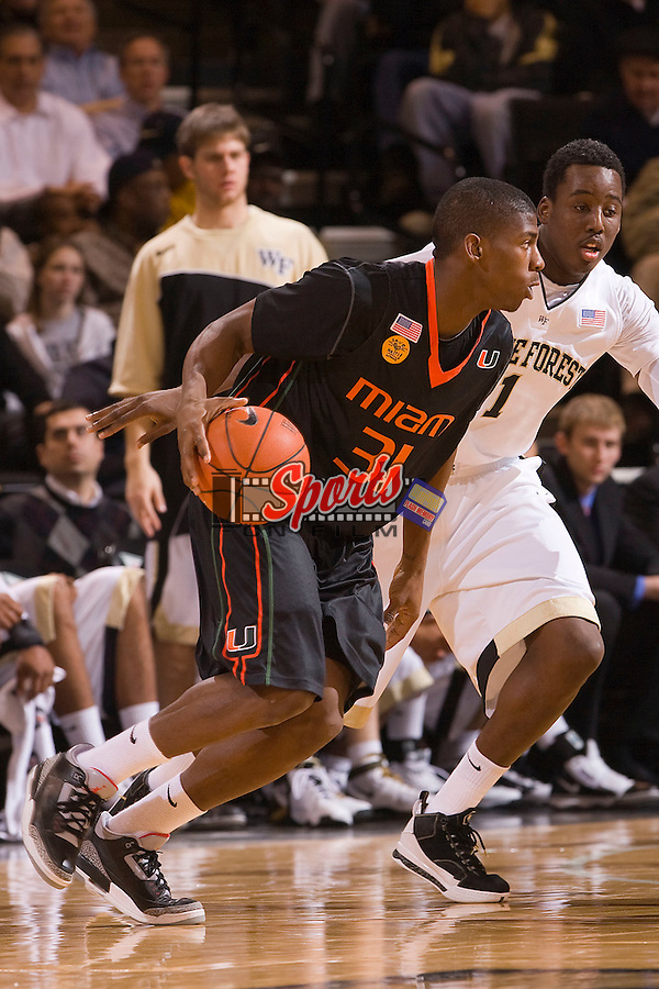 DeQuan Jones #31 of the Miami Hurricanes dribbles past Al-Farouq Amino #1 of the Wake Forest Demon Deacons at the Lawrence Joel Veterans Memorial Coliseum February 2n Winston-Salem, NC.  The Demon Deacons defeated the Hurricanes 64-57.  Brian Westerholt / Sports On Film