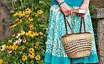 A woman carries a straw purse from Bellagio, Italy while visiting a garden at Villa Monastero in Varenna, Italy on Lake Como
