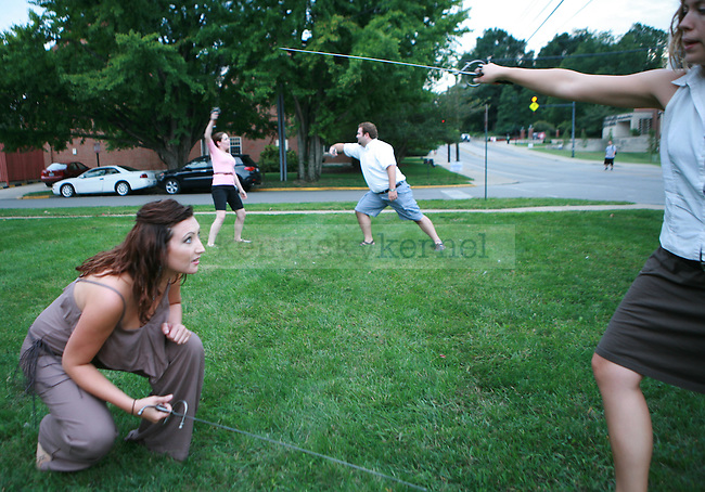 vocal performance sophomore Laikin Simons fights vocal performance sophomore Jacob Waid  (BACK) while Musical Arts Doctoral student Sarah Parker crouches to dodge a swing by vocal performance senior Melissa Snow-Groves on the lawn of the Schmidt Vocal Arts Center in Lexington, Ky., Sept. 14, 2011. Photo by Brandon Goodwin | STAFF