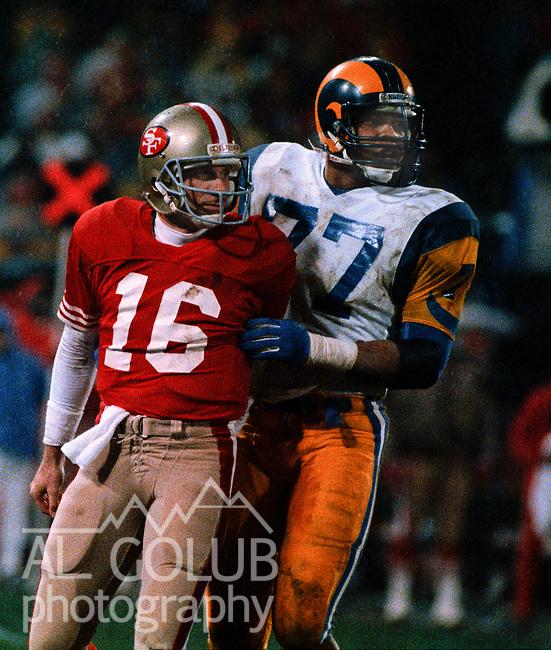 San Francisco 49ers vs Los Angles Rams at Candlestick Park Sunday, December 27, 1987..49ers beat Falcons 48-0.San Francisco 49ers Quarterback Joe Montana (16) and Los Angles Rams Defensive End Gary Jeter (77)..