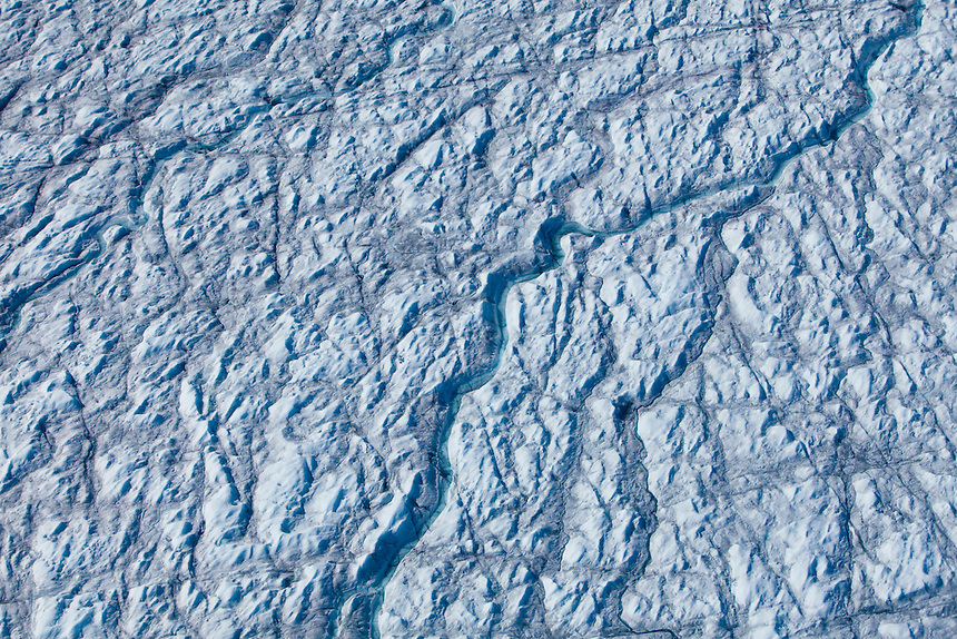 A stream of melt water snakes across the surface of the Greenland Ice Cap, West Greenland, August 2011.  Photo: Ed Giles.
