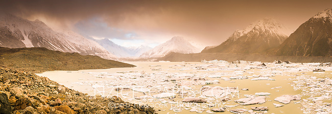 Tasman Glacier and its terminal lake with icebergs and icy debris after massive terminal face calving in 2010 under sunset with passing snowing clouds reflecting sunset colours while snowing, Mt. Cook National Park, Mackenzie Country, World Heritage Area, New Zealand