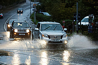 Pictured: Cars travel through the flooded A4119 by Aberdulais Falls in south Wales, UK. Saturday 13 October 2018<br /> Re: Flooding caused by Storm Callum in Aberdulais near Neath, south Wales, UK.