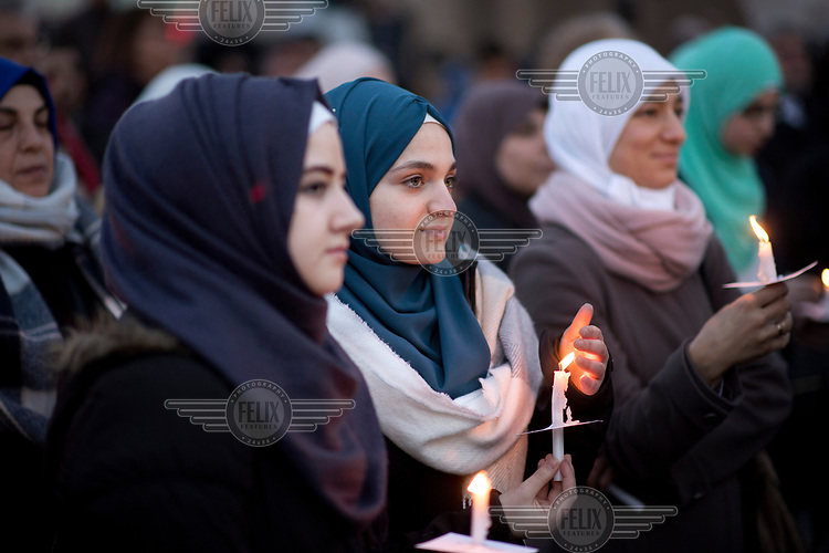 Young Muslim women, holding candles, during a peace rally with the slogan 'Religionen fuer ein weltoffenes Berlin' (Religions for a an open Berlin). It was held in memory of the victims of the Breitscheidtplatz Christmas market terror attack.
