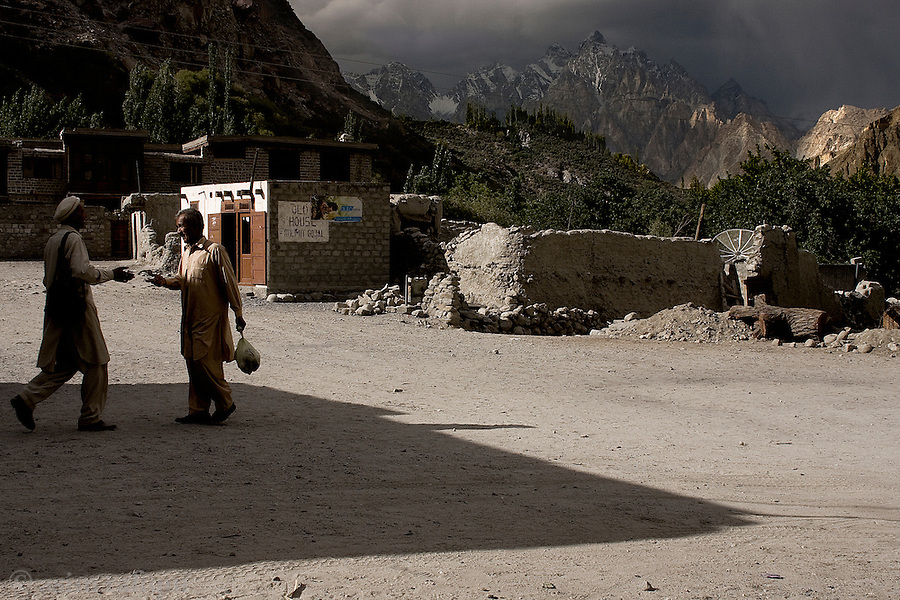 Friends meet in the Gulmit village center, with the imposing peaks of The Cathedral in the background.