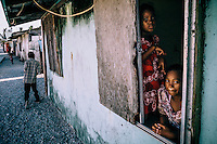 Children look out the window of a house on the island-slum. Ebeye, one of the most densely populated islands in the world and is home to a large number of variously disabled people. Aside from the nearby nuclear testing sites, overcrowding, poor sanitation, and the failure of the US administration to immunise the population of Ebeye has meant that its residents has suffered a high degree of  diseases such as tuberculosis, polio, hepatitis, influenza, measles, cholera etc.