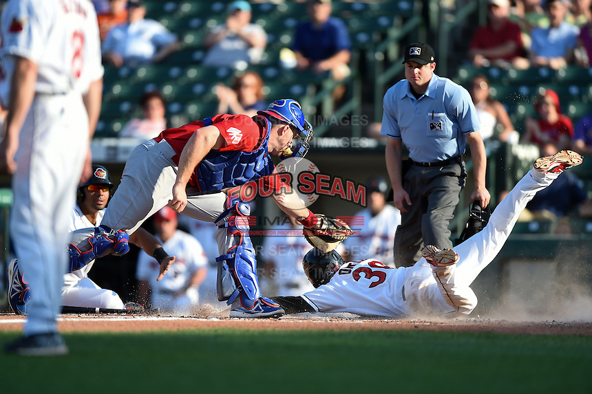 Rochester Red Wings outfielder Daniel Ortiz (39) slides past catcher Erik Kratz (39) as umpire Joseph Born looks on during the second game of a doubleheader against the Buffalo Bisons on July 6, 2014 at Frontier Field in Rochester, New  York.  Rochester defeated Buffalo 6-1.  (Mike Janes/Four Seam Images)