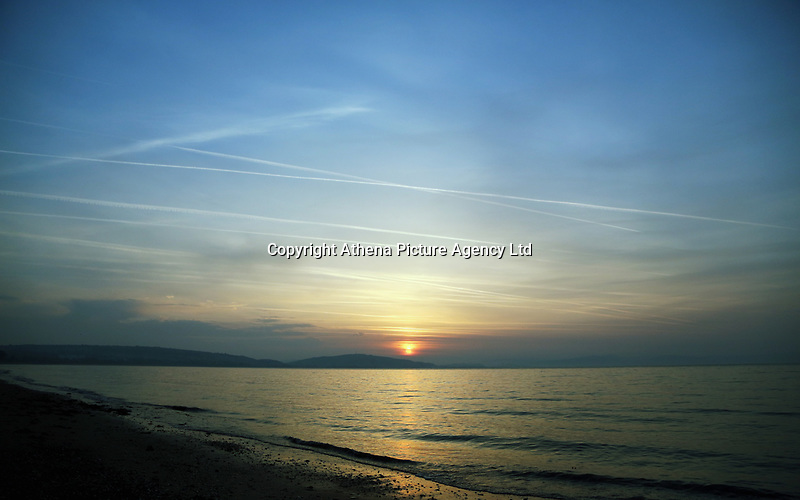 Pictured: The sun rises over Swansea Bay, as seen from West Cross in south Wales, UK. Wednesday 21 June 2017<br /> Re: Summer Solstice