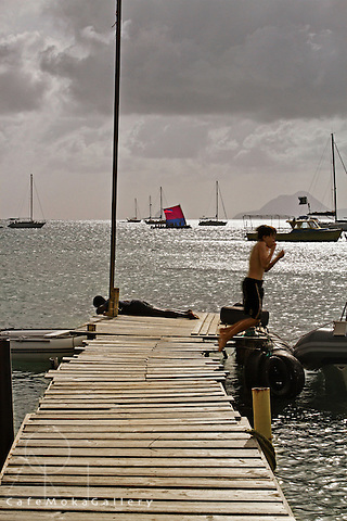 Boys playing on a jetty with a traditional sailing boat (yole) in the background, Martinique