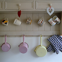 Pastel-coloured enamel saucepans hang from hooks beneath a collection of ceramic mugs in a corner of the kitchen