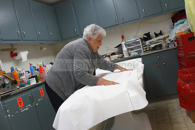 Mary Deaton lays a white cloth sheet onto the embalming table in the embalming room of the Deaton Funeral Home, Friday, Oct. 12, 2011 in Jackson, Ky. Photo by Brandon Goodwin