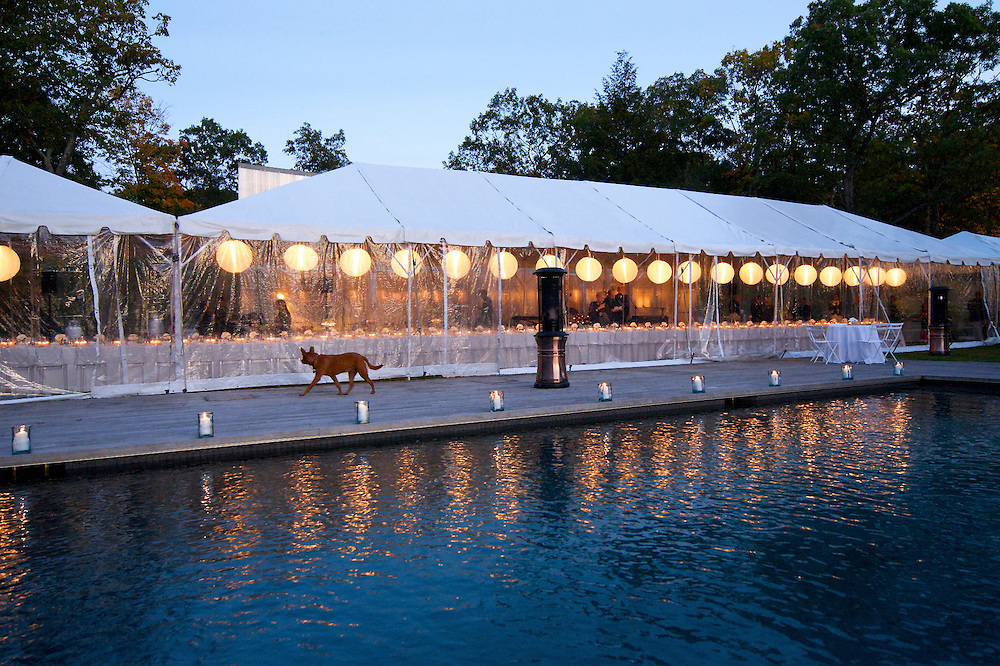 View of the tent and pool at dusk from a dinner party at a private home.