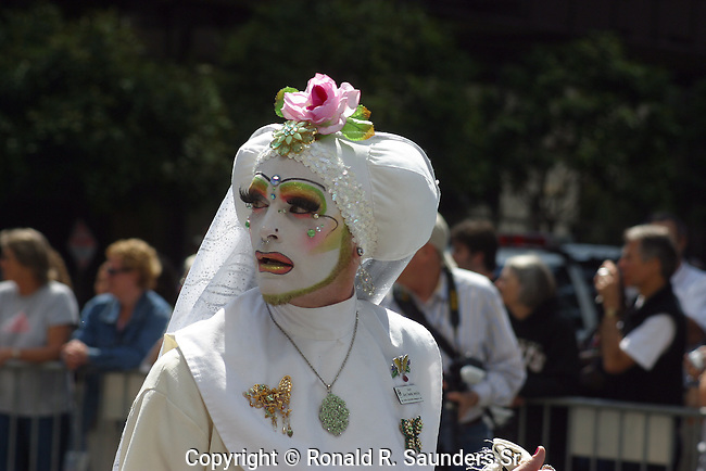 GAY MAN IN WHITE MARCHES IN GAY PRIDE PARADE