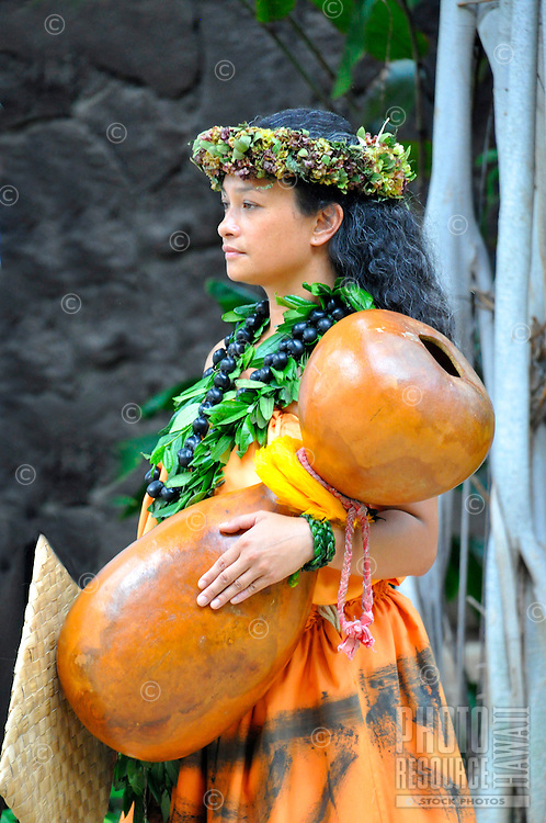 A woman wearing maile leaf and kukui nut lei holds an ipu heke (double gourd, a rhythm instrument) prior to a kahiko (ancient style) hula performance in Waikiki, O'ahu.
