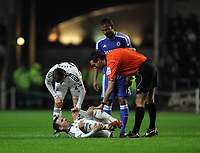 Pictured: Leon Britton of Swansea on the ground is being spoken to by match referee A Marriner (R), after being tackled by Florent Malouda of Chelsea (C). Tuesday, 31 January 2012<br />