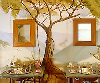 Seemingly suspended from a painted acacia tree which forms part of the mural on this bathroom wall are two wooden mirrors and matching safari-style washstands