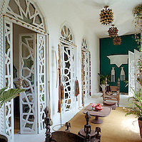 A series of double doors with a star inspired pattern line the wall of this living room furnished with tribal thrones