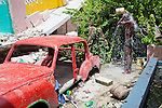 A man bathes near the rubble of a former school on July 7, 2010 in Port-au-Prince, Haiti.