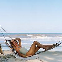 Portrait of Charlene de Ganay reclining in a hammock on the beach