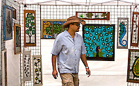 A visitor to Charlotte's Festival in the Park looks over artwork available for purchase.  For more than four decades, Charlotte's annual Festival in the Park has brought music, art and fun to Charlotteans and visitors. The festival has been chosen as one of Sunshine Artists Magazine's 200 Best Festivals.