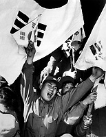 This anti-Communist North Korean just released from a prisoner of war camp is serving as a kind of cheerleader for fellow ex-POW's as they shout their joy of reaching Seoul.  The flags are of the Republic of South Korea.  Ca. 1953-54.  Gravy. (USIA)<br /> Exact Date Shot Unknown<br /> NARA FILE #:  306-PS-54-1497<br /> WAR & CONFLICT BOOK #:  1497
