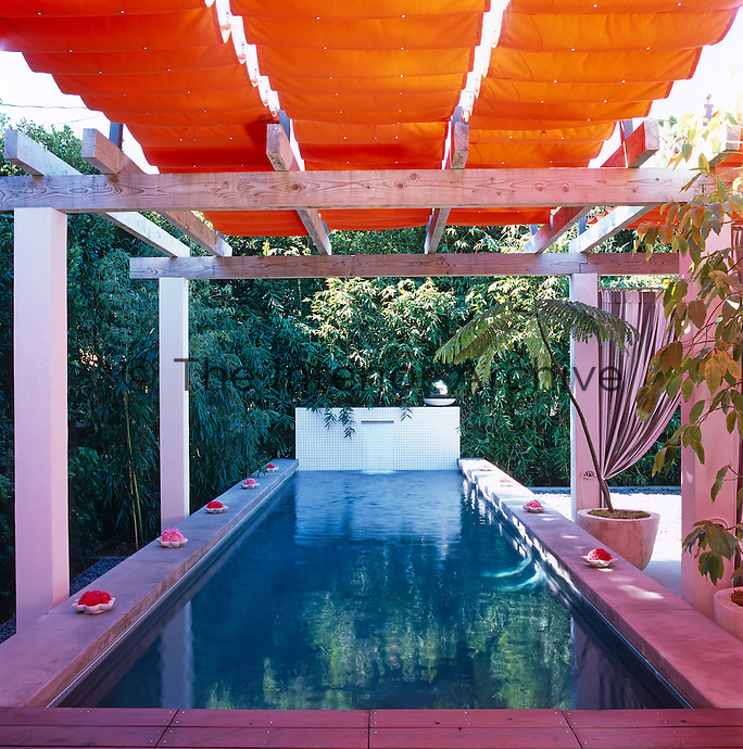 The pool and patio have taken over the entire backyard of the property shaded by a pergola with a retractable orange awning