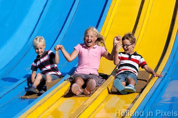Kinderen op de glijbaan in de Linnaeushof in Bennebroek. Twee broertjes en hun zus