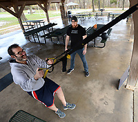 "Tim Watson (left), an attorney in Fayetteville, performs pistol squats Tuesday, March 24, 2020, with the help of health coach Jim Goza as Watson prepares for his wedding in June at Veterans Memorial Park in Fayetteville. Goza works for Club Haus Fitness and is meeting club members outside for workouts to allow for fitness with social distancing now that the gym has closed because of the covid-19 pandemic. ""We are doing everything we can do to stay as innovative as possible. Right now we all need to be as healthy as possible,"" Goza said. Visit nwaonline.com/200325Daily/ for today's photo gallery.<br /> (NWA Democrat-Gazette/Andy Shupe)"