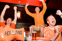 Netherlands fans (L-R) Mark Geenevasen, Sander Geenevasen, and Niels Cornet watch their team's match against the Ivory Coast at Tonic, a New York City nightclub, on June 16, 2006.<br /> <br /> The World Cup, held every four years in different locales, is the world's pre-eminent sports tournament in the world's most popular sport, soccer (or football, as most of the world calls it).  Qualification for the World Cup is open to any country with a national team accredited by FIFA, world soccer's governing body. The first World Cup, organized by FIFA in response to the popularity of the first Olympic Games' soccer tournaments, was held in 1930 in Uruguay and was participated in by 13 nations.    <br /> <br /> As of 2010 there are 208 such teams.  The final field of the World Cup is narrowed down to 32 national teams in the three years preceding the tournament, with each region of the world allotted a specific number of spots.  <br /> <br /> The World Cup is the most widely regularly watched event in the world, with soccer teams being a source of national pride.  In most nations, the whole country is at a standstill when their team is playing in the tournament, everyone's eyes glued to their televisions or their ears to the radio, to see if their team will prevail.  While the United States in general is a conspicuous exception to the grip of World Cup fever there is one city that is a rather large exception to that rule.  In New York City, the most diverse city in a nation of immigrants, the melting pot that is America is on full display as fans of all nations gather in all possible venues to watch their teams and celebrate where they have come from.
