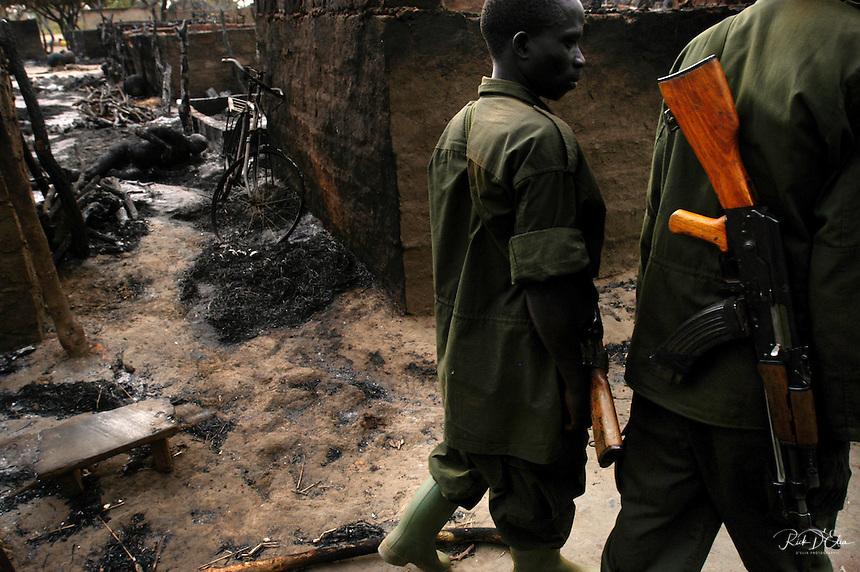 Amuka Militia patrol Barlonyo IDP camp near Lira, Uganda two days after more than 300 people were massacred by Joseph Kony's Lords Resistance Army in January 2004. Kalashnikov AK-47.