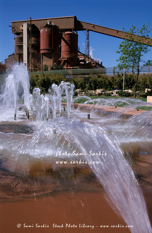 Flowing water fountains with a Bauxite Refinery in the background, Gardanne, Provence, France.