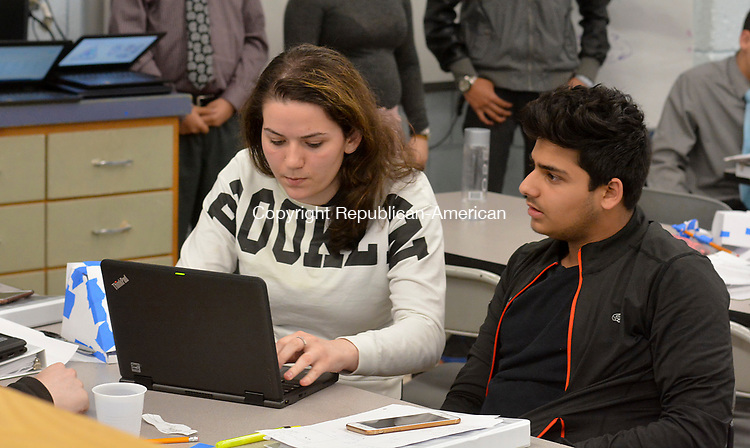WATERBURY, CT-050517JS11- Students Alba Gashi and Nibras Malik work on their teams proposal Friday at Crosby High School in Waterbury. The students received help and advice by Gregory N. Polletta, a 1989 graduate of Crosby,  current professor of Engineering and founder of iGNITIATE. The students worked on proposals that will be presented to Sikorsky. The teams developed a product and worked engineering, production, out price points, funding and profits. <br /> Jim Shannon Republican-American