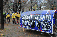 November 23, 2011, Toronto Police deployed in significant numbers this morning, beginning the process of evicting the Occupy Toronto tent camp from St. James Park.  Here, three police constables are seen near the Occupy Toronto Movement covered wagon.